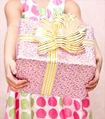 Little Girl Holding Christmas Gift Box In The Foreground
