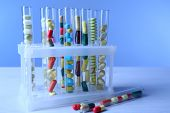 Different color drugs in test tubes, on wooden table, on color background