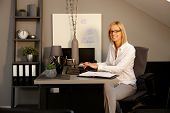Happy blonde woman sitting at desk in office, working with laptop computer, smiling, looking at camera.
