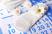Sanitary pads and white flowers on blue calendar background