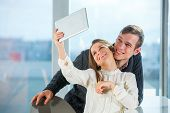 Beautiful couple taking selfie photo in cafe, selective focus