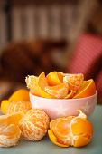 Sweet tangerines and oranges on table in bowl in room