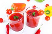 Tomato juice in glasses and fresh vegetables on light wooden background
