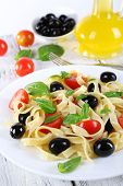 Spaghetti with tomatoes, olives and basil leaves on plate on wooden background