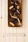 stock photo of pastarelle  - Miniature eclairs in a wooden plate with a narrow piece of paper for information - JPG
