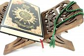 stock photo of quran  - stand with Quran and green rosary before light background
