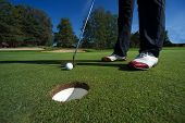 Golf putting and red shoes