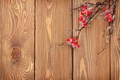 Christmas wooden background with holly berry branch and copy space