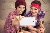 Two Brunette teenage girls friends in hipster outfit with a skat