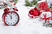 Red vintage alarm clock in the snow