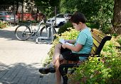 image of 7-year-old  - Side shot of a smart 7 years old boy reading a book in a park - JPG