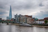 Downtown London architecture with buildings along the banks of the River Thames and the Shard in the background on a grey overcast day