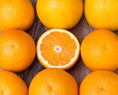 picture of sukkot  - many whole fresh oranges with one half of orange in center on wooden background - JPG