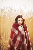 Brunette woman in plaid on a park near lake. autumn weather. cold.