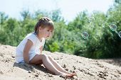 Curious little model sitting on sand in park