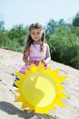 Beautiful little girl posing with paper sun