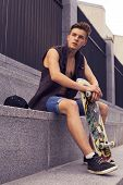 Young Blonde Guy On Skateboard In Casual Outfit In The Urban City Outdoors. Active. Sport