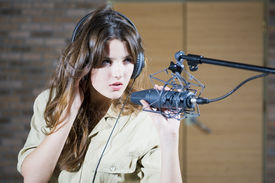 foto of recording studio  - Young beautiful retro woman recording the sound in professional studio with mic and phones - JPG