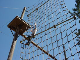 stock photo of boy scout  - boy scout climbs rope climb - JPG