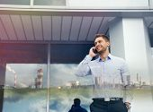 stock photo of enterprise  - double exposure of businessman with phone device and industrial enterprise on urban building background - JPG