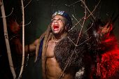 pic of werewolf  - Muscular werewolf hair dreadlocks among the branches of the tree screaming - JPG