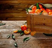 stock photo of wooden crate  - Wooden crate with tasty tangerines on a table - JPG