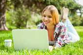 picture of lie  - Beautiful young female student working on laptop and smiling while lying on the grass in park - JPG