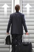 picture of escalator  - Businessman Front Escalator With trolley bag and graphic Arrows - JPG