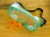 pic of noise pollution  - Protective eyeglasses and ear plugs with cord against a wooden background - JPG