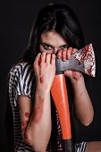 stock photo of bloody  - Young woman with a big bloody axe over black background - JPG