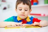image of storybook  - Cute little boy is reading book while sitting at table indoor shoot - JPG