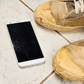 foto of ceramic tile  - Smart phone with the broken screen over the ceramic floor tiles next to a pair of dirty working shoes - JPG