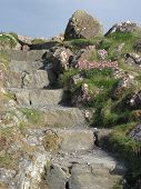 stock photo of stepping stones  - Uneven Stone Steps Climbing Up Hill to Nowhere - JPG