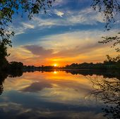 stock photo of hamlet  - Sun and sky with clouds reflected in the water of the lake on the shores of which grow trees at sunrise - JPG