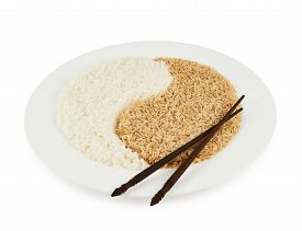 foto of yin  - Plate of brown and white rice forming a yin yang sign with the eating sticks lying on top of it - JPG