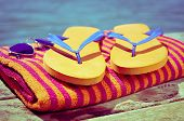 ������, ������: a pair of sunglasses a pair of flip flops and a beach towel on a wooden boardwalk with the sea a