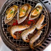 picture of roster  - Closeup grilled seafood prawns and squids on fire background - JPG
