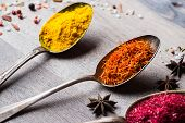 image of saffron  - Different spices selection in old metal spoons over wooden background - JPG