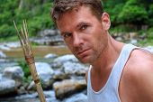 pic of primitive  - Closeup portrait of handsomely rugged Caucasian man with primitive bamboo spear in natural setting of jungle river environment - JPG