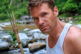 image of primite  - Closeup portrait of handsomely rugged Caucasian man with primitive bamboo spear in natural setting of jungle river environment - JPG