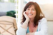 Attractive Middle Aged Woman Smiles On The Patio. poster