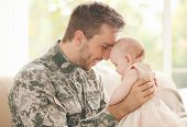 Military father holding his newborn baby poster