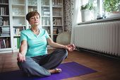 Senior woman meditating in lotus position at home poster