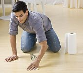 A man cleaning up a spilled glass of water.  He is using paper towels on a wood floor. Horizontally framed photo.