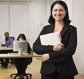 An attractive brunette is holding file folders and is smiling at the camera. There are people workin