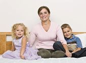 A mother sits on a bed with her son and daughter as they smile at the camera. Horizontally framed shot.