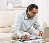A man paying his bills online.  He has a checkbook in his hand.  Square framed shot.