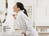 A young woman is standing in front of the bathroom mirror and brushing her teeth.  Horizontally fram