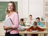 stock photo of student teacher  - Teacher standing with notebook in classroom - JPG
