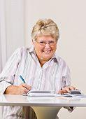 Mulher sênior escrever cheques